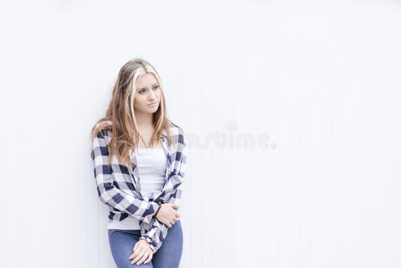 Nachdenkliche schöne junge Frau auf dem weißen Hintergrund, der weg schaut lizenzfreie stockbilder