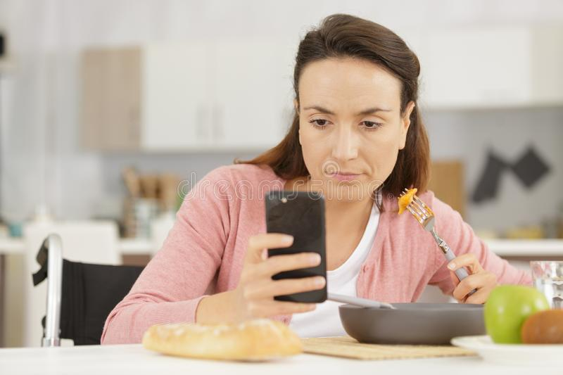 Nachdenkliche simsende Frau beim Essen lizenzfreie stockbilder