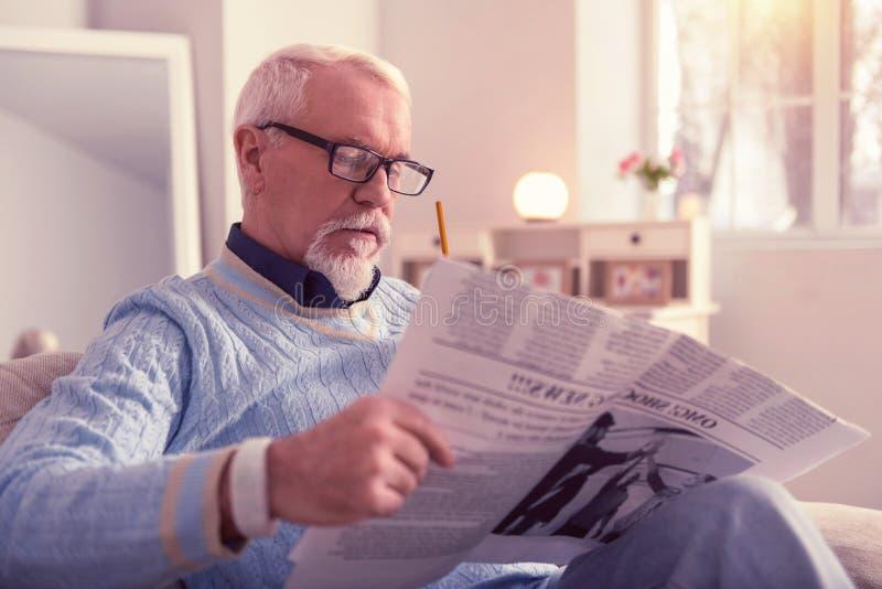 Nachdenkliche starke lesende neue Nachrichten des älteren Mannes stockfotografie