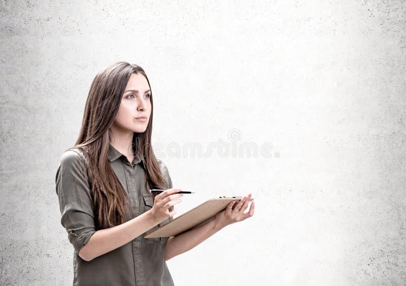 Nachdenkliche zufällige Frau mit dem Klemmbrett, Schein oben lizenzfreie stockfotografie