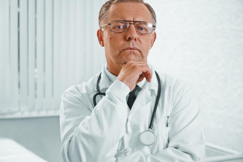 Nachdenklicher älterer Doktor lizenzfreie stockfotografie