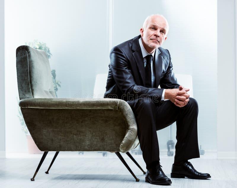 Nachdenklicher älterer Geschäftsmann, der in einem Lehnsessel sitzt stockbild