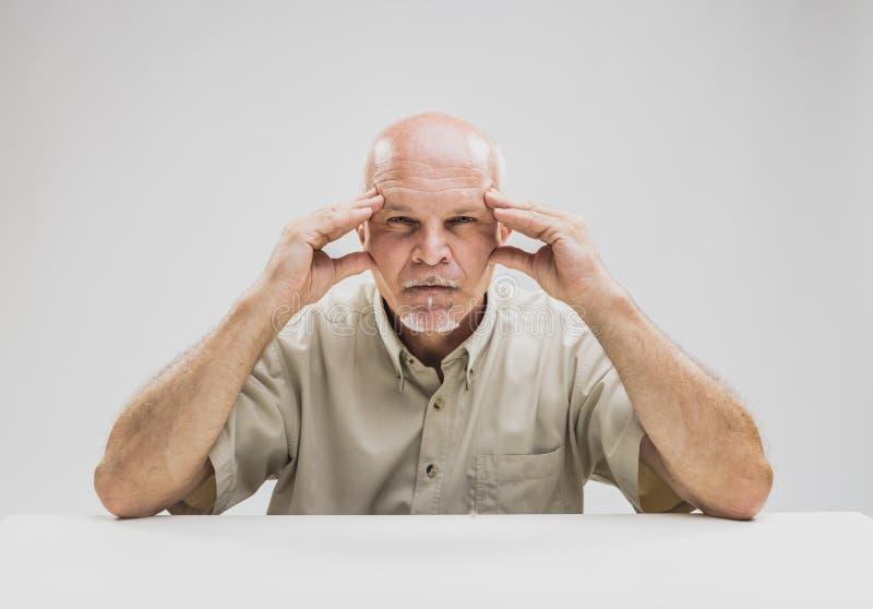 Nachdenklicher älterer Mann mit einem fokussierten Ausdruck lizenzfreie stockfotos