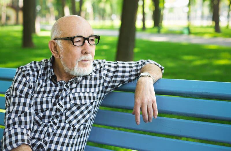 Nachdenklicher älterer Mann in zufälligem draußen stockfoto