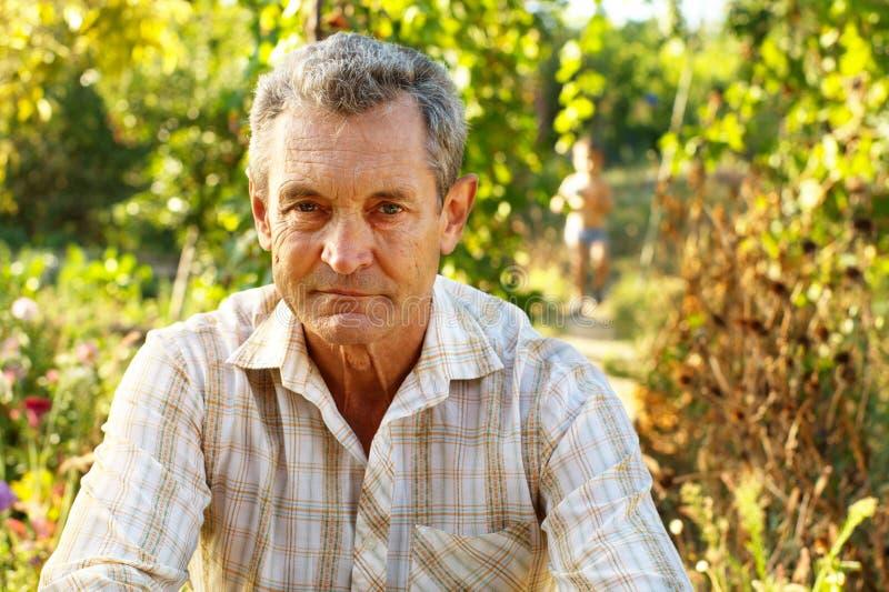 Nachdenklicher alter Mann im Garten lizenzfreie stockfotos