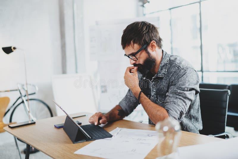 Nachdenklicher bärtiger Designer, der am modernen Bürodachboden arbeitet Mitarbeiter, der elektronischen Notentablet-computer auf stockfotos