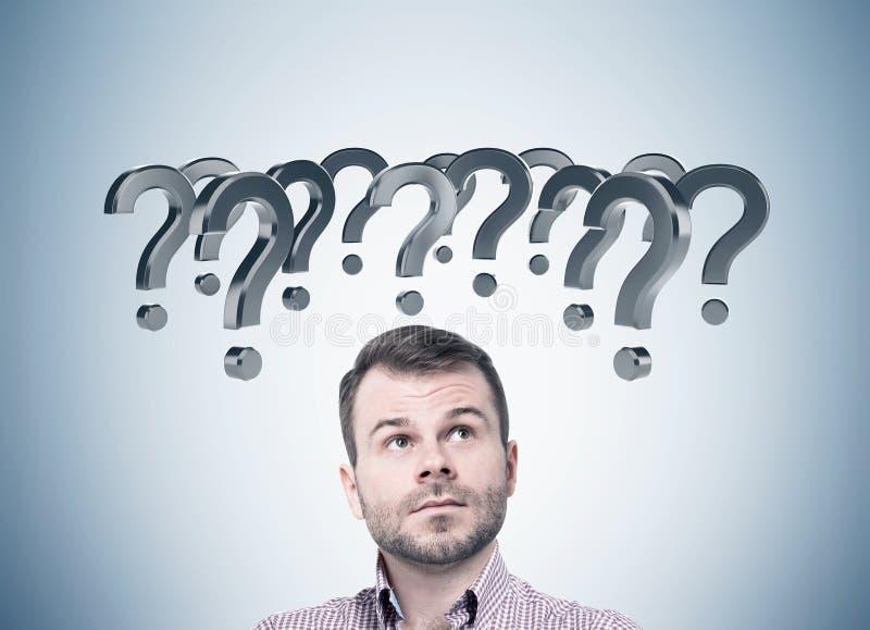 Nachdenklicher bärtiger Mann und graue Fragezeichen stockbild