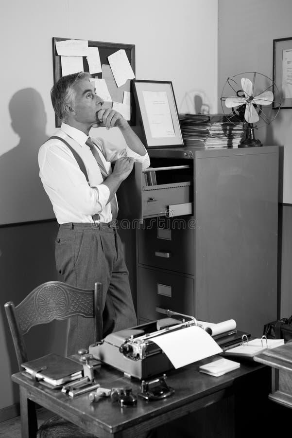 Nachdenklicher Büroangestellter, welche nach einer Datei im Kabinett sucht stockbilder