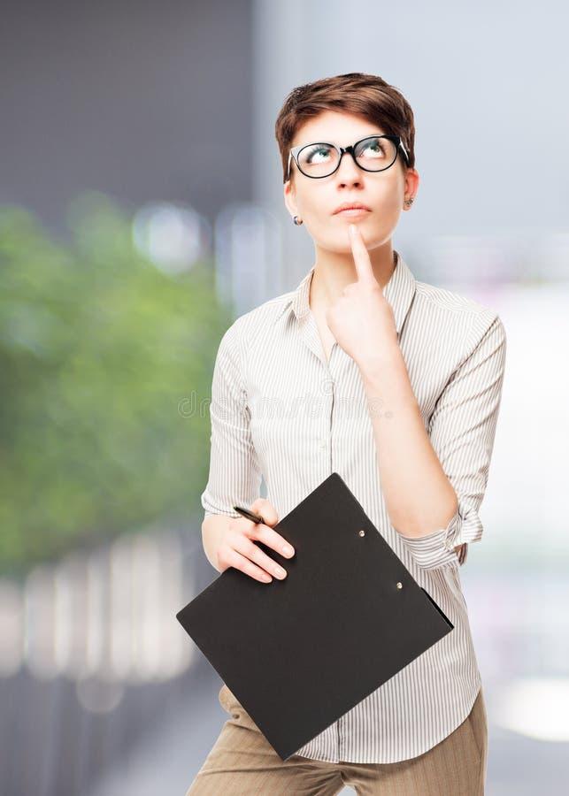Nachdenklicher Buchhalter in den Gläsern mit einem Ordner, der oben schaut lizenzfreies stockfoto