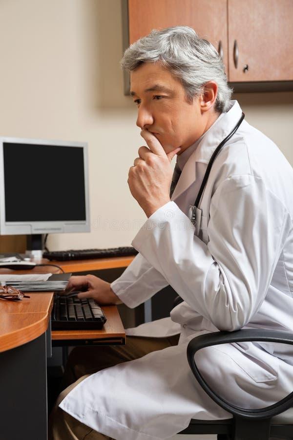 Nachdenklicher Doktor Sitting At Desk lizenzfreies stockbild