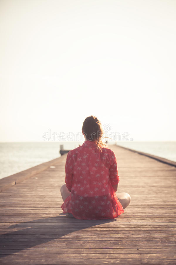 Nachdenklicher Frauentourist, der auf hölzernem Pier am Strand während des Sonnenuntergangs sitzt und Unendlichkeitsansicht in Ri lizenzfreies stockbild