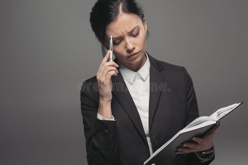 Nachdenklicher Geschäftsfraubehälter und -tagebuch bei der Planung ihrer Arbeit stockfotos