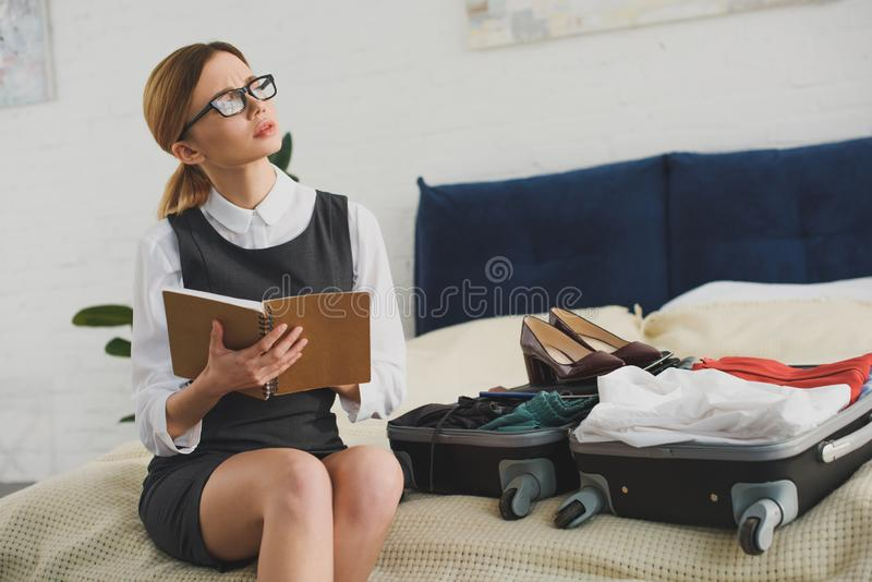 nachdenklicher Geschäftsfrauholdingplaner beim Verpacken des Koffers stockfoto