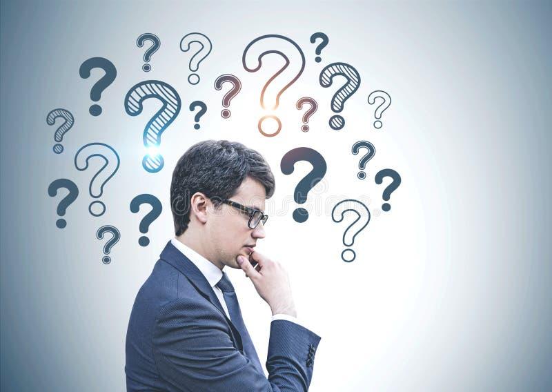 Nachdenklicher Geschäftsmann in den Gläsern, Fragezeichen lizenzfreie stockbilder