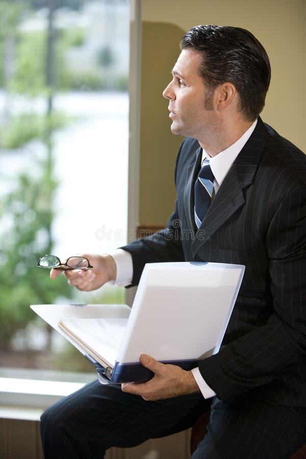Nachdenklicher Geschäftsmann, der heraus Fenster schaut lizenzfreie stockfotografie