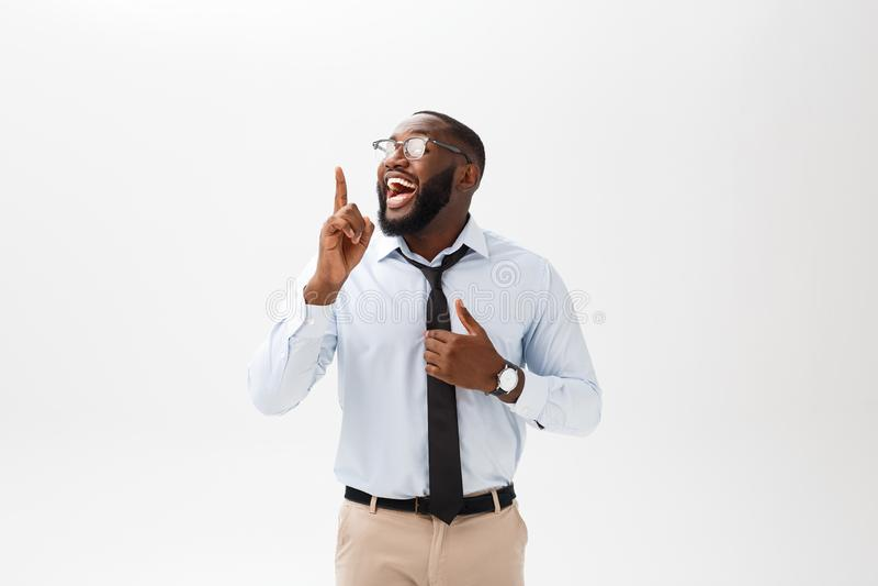 Nachdenklicher Geschäftsmann des jungen Afroamerikaners steht im Büro mit der Hand in der Front, erhält Geschäftsinspiration stockfotos