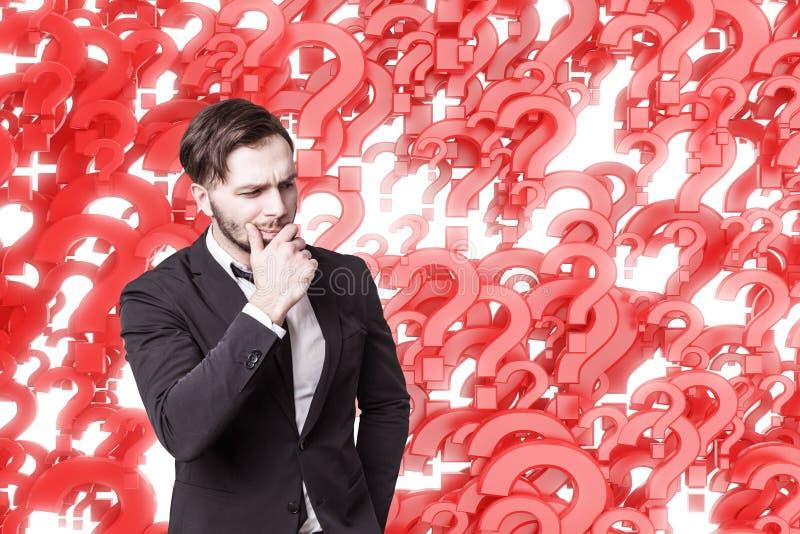 Nachdenklicher Geschäftsmann und rote Fragezeichen stockfotos