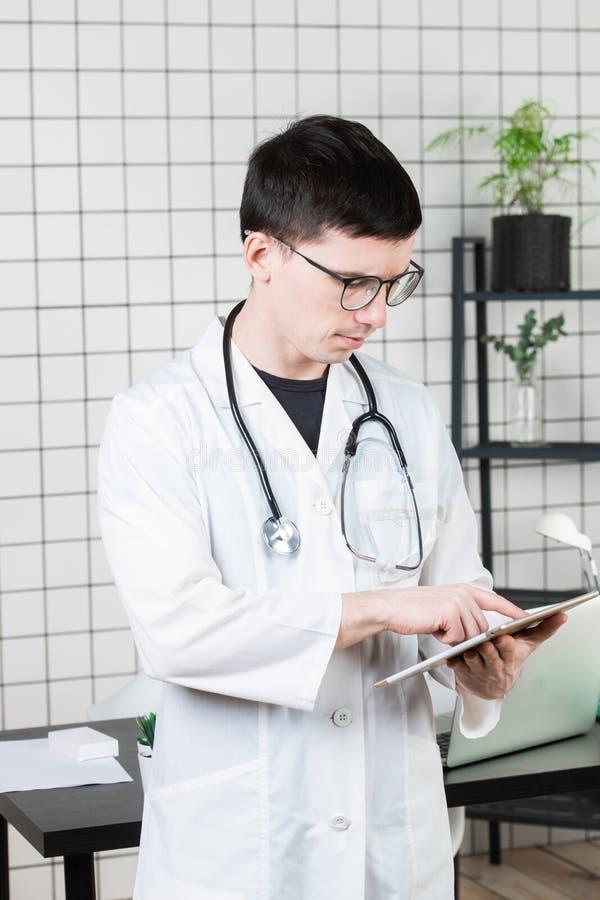 Nachdenklicher hübscher junger männlicher Doktor unter Verwendung des Tablet-Computers Technologien im Medizinkonzept lizenzfreie stockfotografie