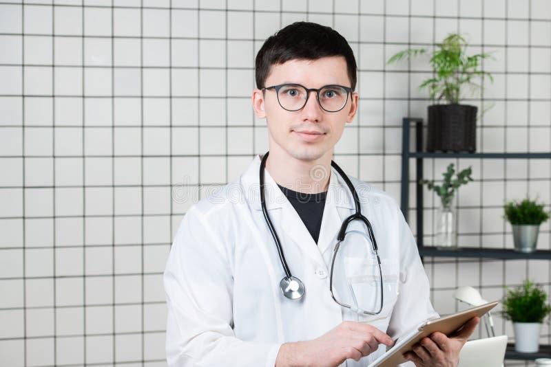 Nachdenklicher hübscher junger männlicher Doktor unter Verwendung des Tablet-Computers Technologien im Medizinkonzept lizenzfreies stockfoto