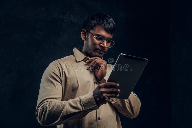 Nachdenklicher indischer Mann im Eyewear und im Hemd unter Verwendung eines Tablet-Computers im Studio lizenzfreie stockfotos