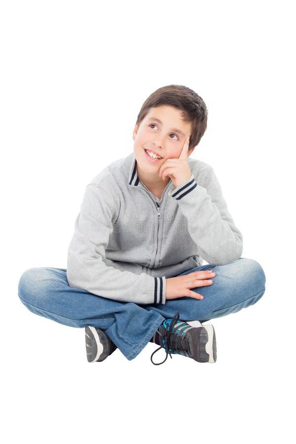 Nachdenklicher jugendlicher Junge, der auf dem Boden sitzt stockfoto