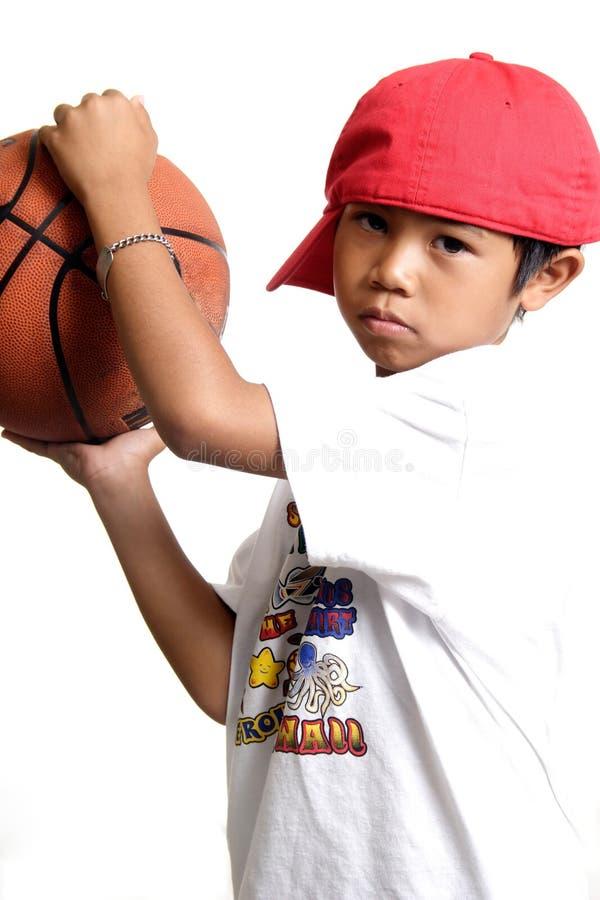 Nachdenklicher Junge, der einen Basketball anhält stockfotos