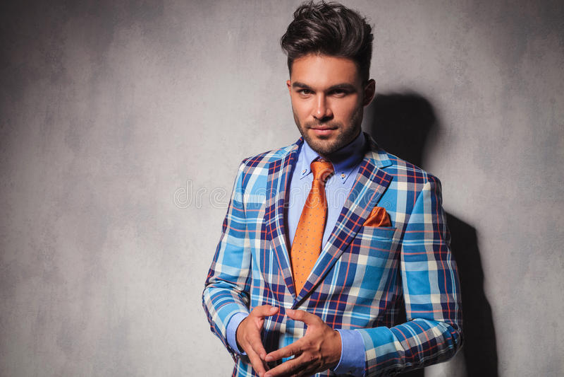 Nachdenklicher junger Mann im Plaidanzug und in der orange Bindungsstellung stockfotos