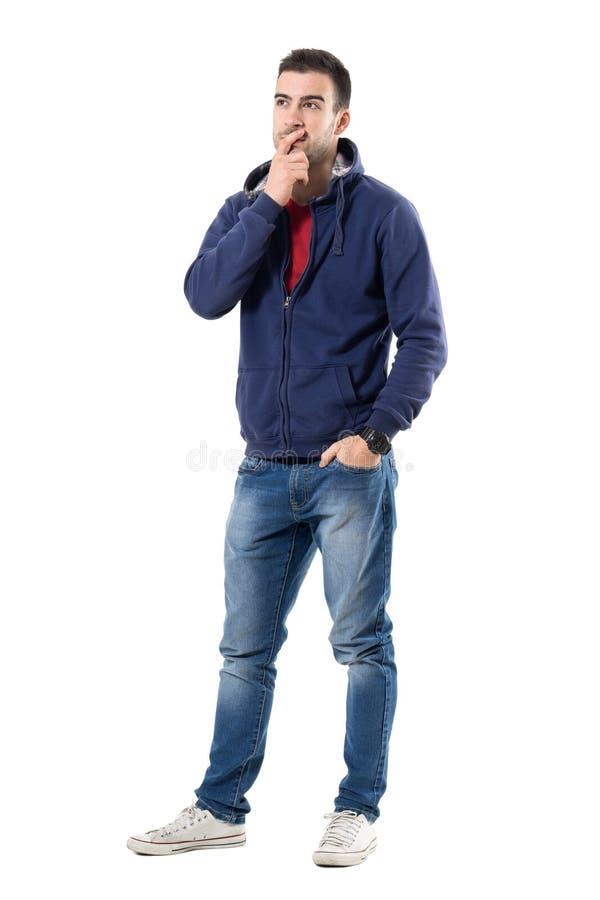 Nachdenklicher junger zufälliger Kerl mit der Hand auf dem Kinn, das oben interessiert schaut lizenzfreie stockbilder