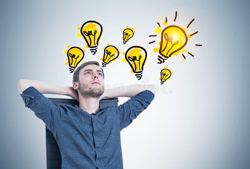 Nachdenklicher Kerl in einem Lehnsessel, gute Ideen lizenzfreie stockbilder