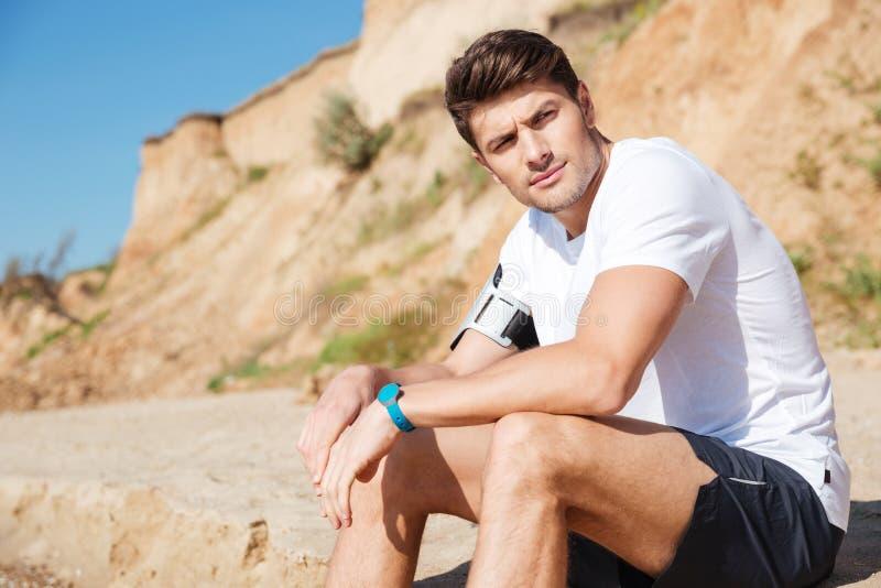 Nachdenklicher Mann, der auf dem Strand sitzt lizenzfreies stockbild