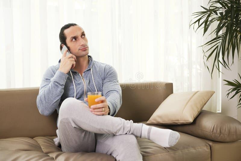 Nachdenklicher Mann, der am Telefon spricht stockbild