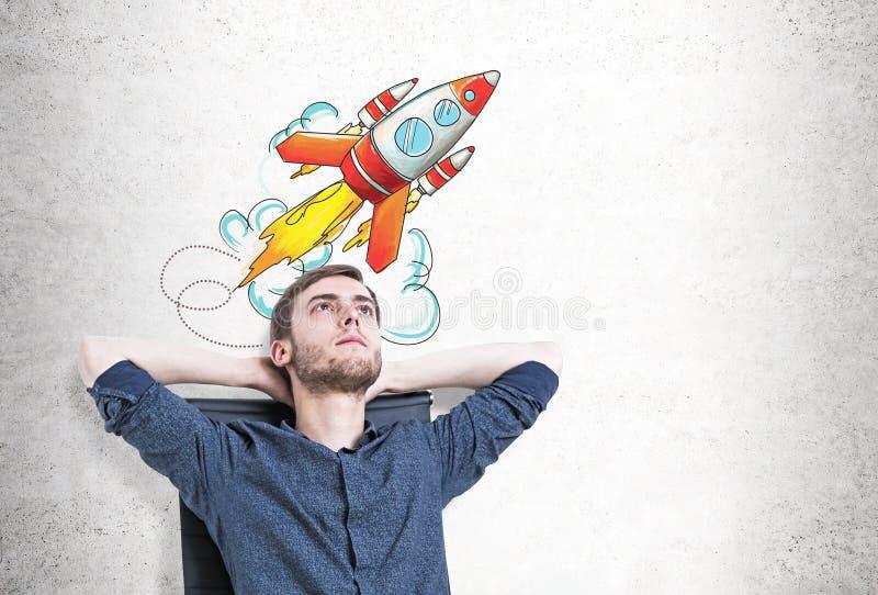 Nachdenklicher Mann im Lehnsessel, laufen Rakete an lizenzfreies stockfoto
