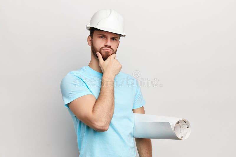 Nachdenklicher Mann mit der Hand auf seinem Kinn, welches die Kamera betrachtet lizenzfreie stockfotos