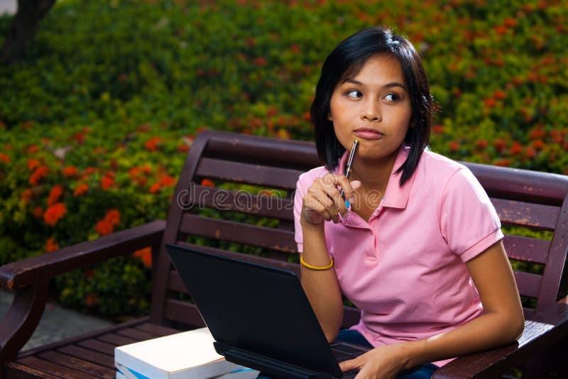Nachdenklicher netter Student-Bank-Laptop stockfoto