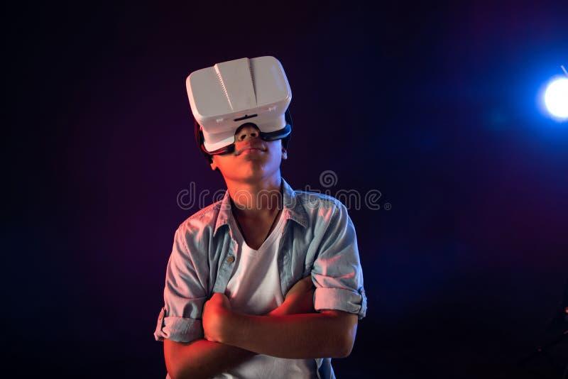 Nachdenklicher Schüler, der einen modernen VR-Kopfhörer trägt stockbild