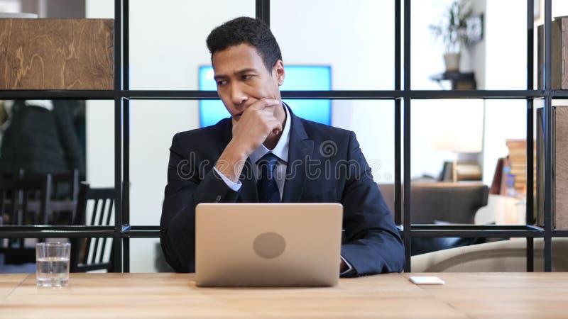 Nachdenklicher schwarzer Geschäftsmann Working auf Laptop lizenzfreies stockbild