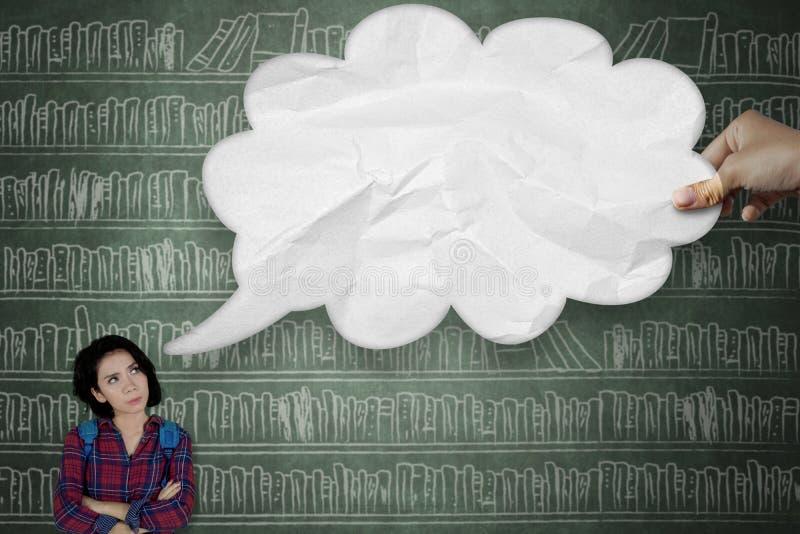 Nachdenklicher Student, der Wolkenblase betrachtet lizenzfreies stockfoto