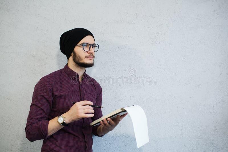 Nachdenklicher Verfassermann, der ein Notizbuch und einen Bleistift hält Bärtig und mit Hemd und schwarzem Hut, tragende Gläser a lizenzfreie stockfotos