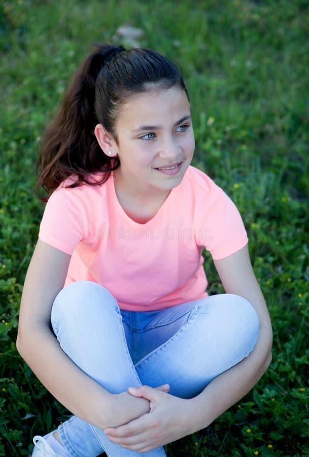 Nachdenkliches jugendliches Mädchen mit den blauen Augen, die auf dem Gras sitzen stockbilder