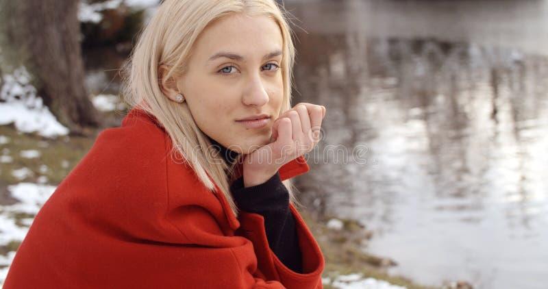 Nachdenkliches junges Mädchen, das Winter in einem Stadtpark genießt stockbild