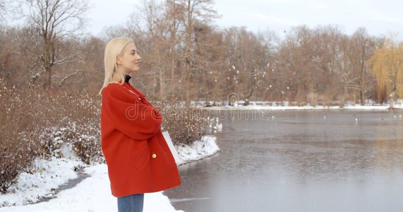 Nachdenkliches junges Mädchen, das Winter in einem Stadtpark genießt lizenzfreies stockbild