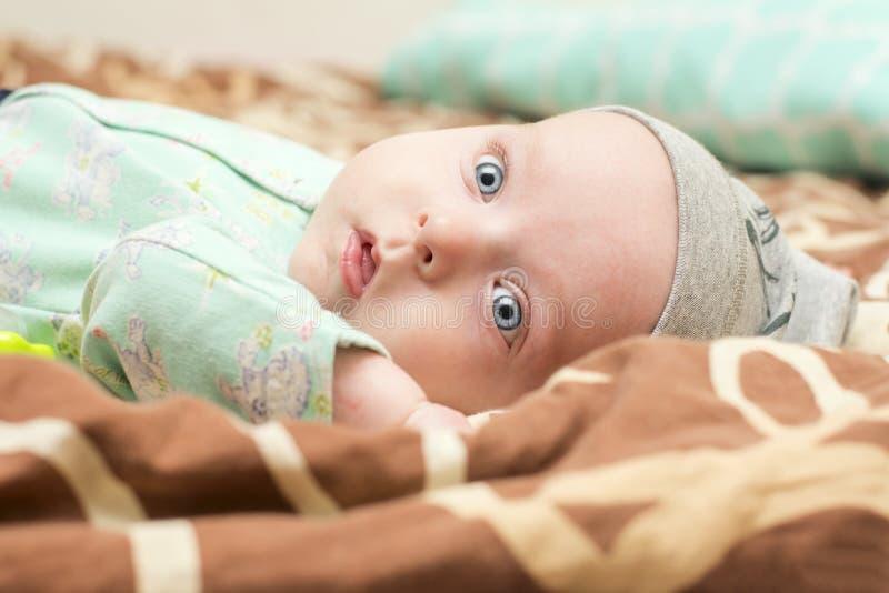 Nachdenkliches Kind, das auf dem Bett liegt lizenzfreie stockbilder