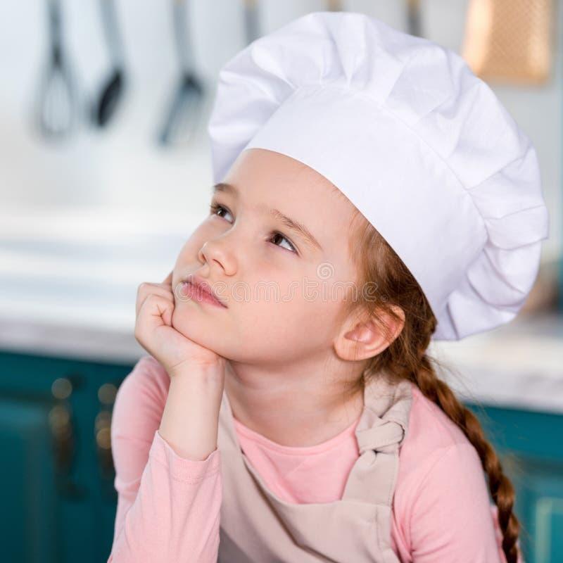 nachdenkliches kleines Kind im Chefhut, der Hand auf Kinn hält und weg schaut stockfoto