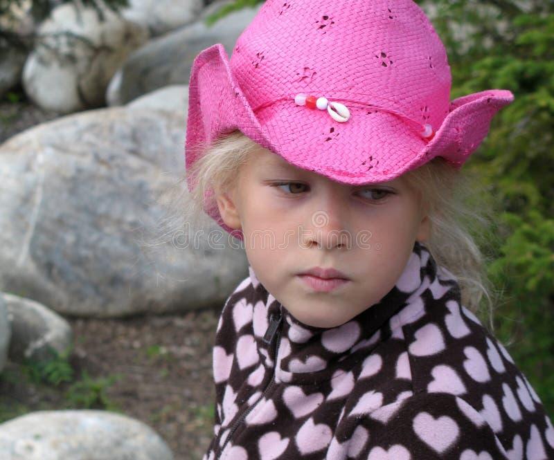 Nachdenkliches kleines Mädchen des Gesichtes in einem rosa Cowboyhut mit einer Muschel stockfotos