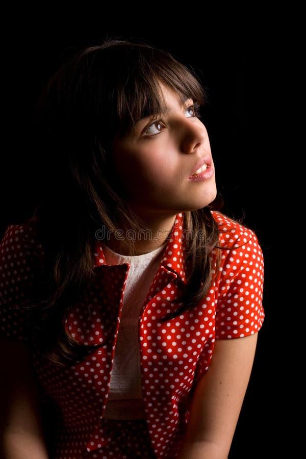 Nachdenkliches oder trauriges Brunettemädchen über dunklem Hintergrund stockbild