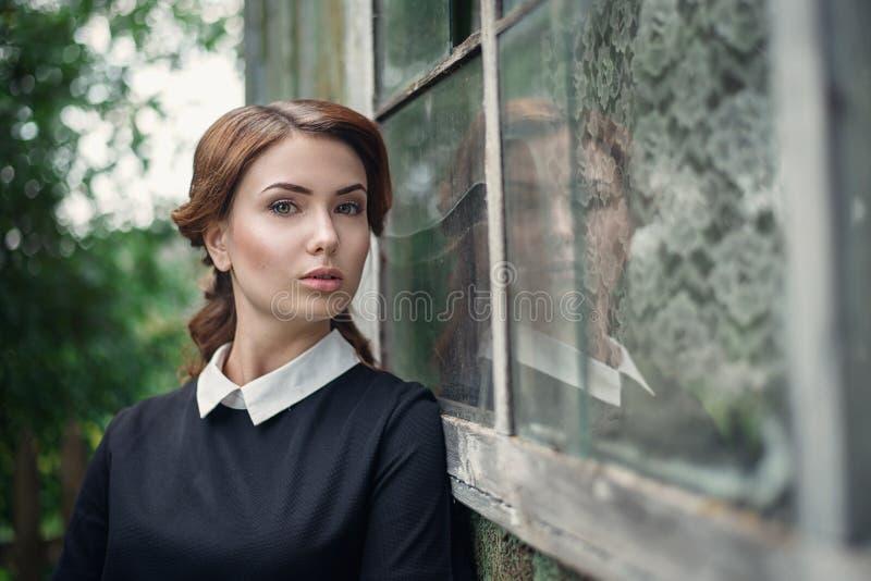 Nachdenkliches schönes junges Mädchen im Retrostilkleid, das nahe dem Fenster des alten Holzhauses steht stockbilder