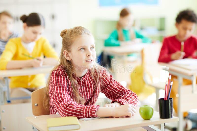 Nachdenkliches Schulmädchen an der Lektion lizenzfreies stockfoto