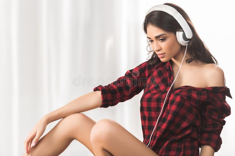 nachdenkliches sexy Mädchen in hörender Musik des karierten Hemdes in den Kopfhörern lizenzfreies stockbild