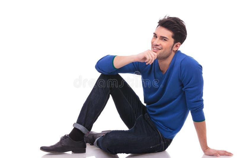 Nachdenkliches Sitzen des jungen Mannes stockbild