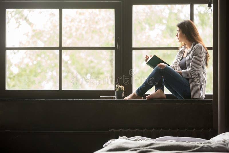 Nachdenkliches träumerisches Mädchen, welches das Buch zu Hause sitzt auf Schwelle hält lizenzfreies stockbild